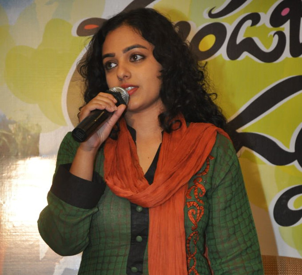 Nithya Menon on stage speaking during a function