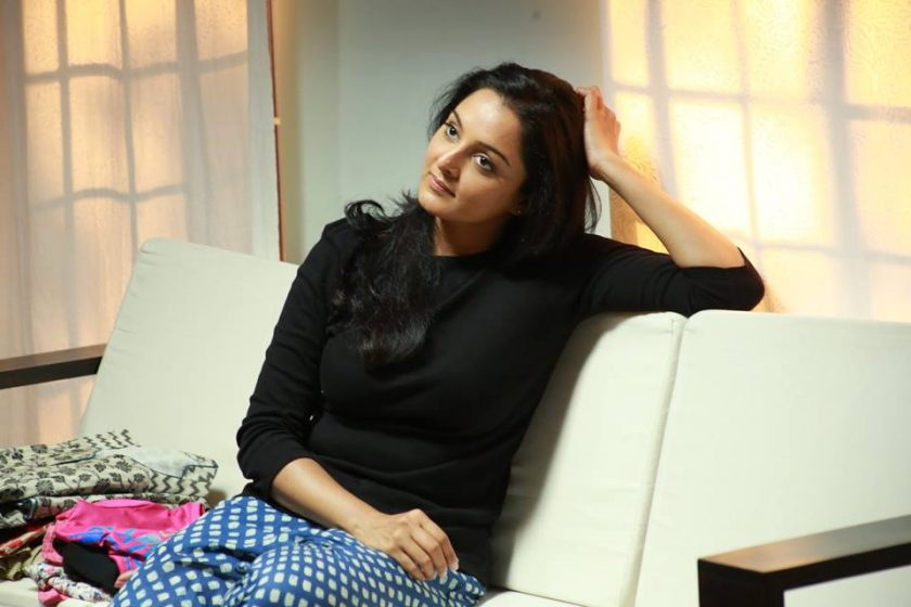 Manju warrier in black top sitting on a sofa