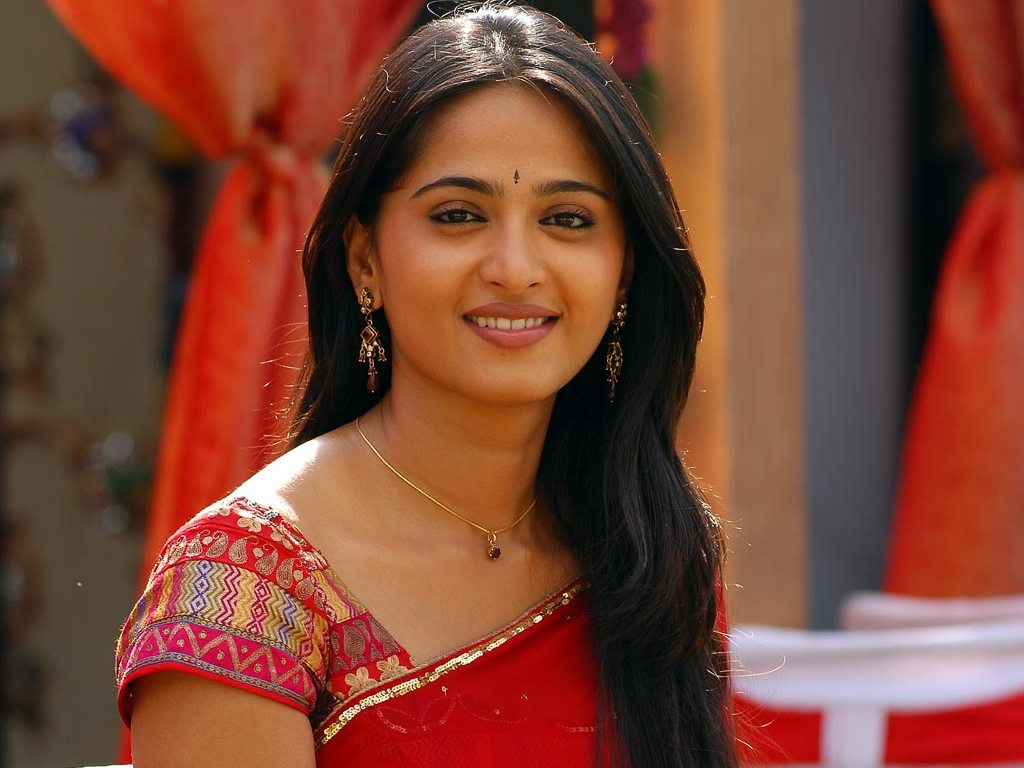 Anushka Shetty smiling in red saree